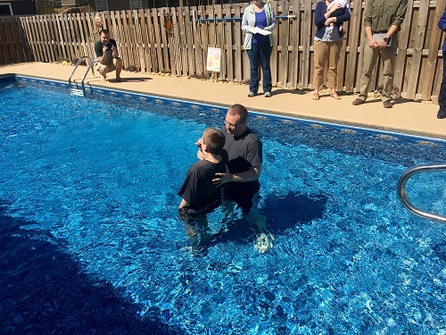 a boy being baptized in a swimming pool