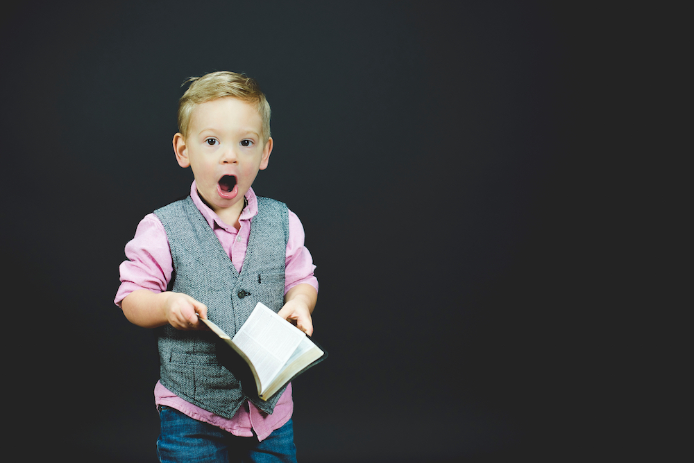 Kid holding a Bible with mouth open