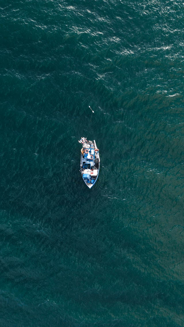 overhead of boat on open ocean - photo by Kristaps Ungurs