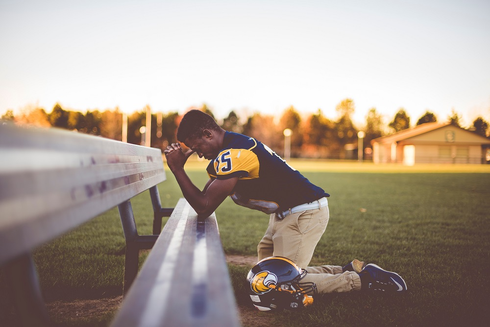 football player praying near the bench