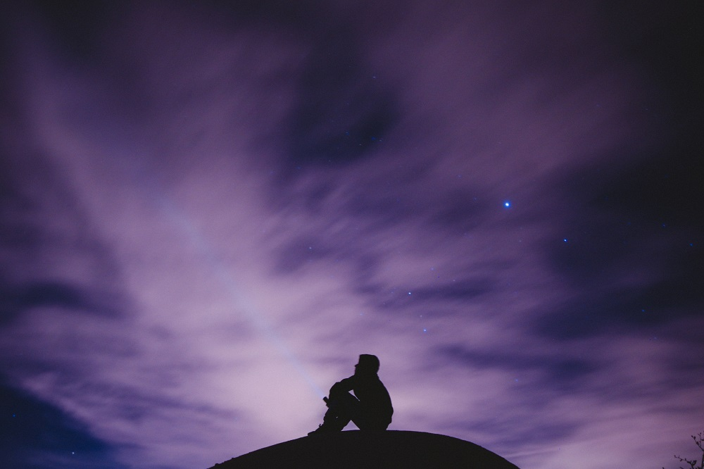 man sitting underneath a purple sky with stars