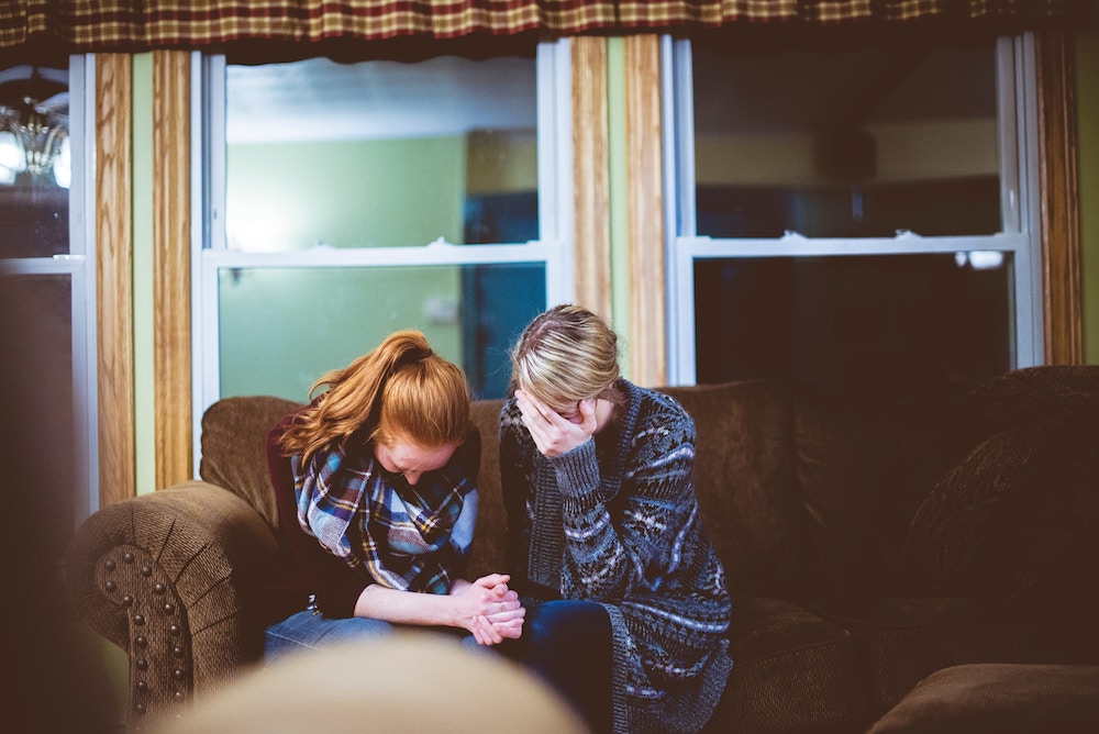 two women praying on a couch