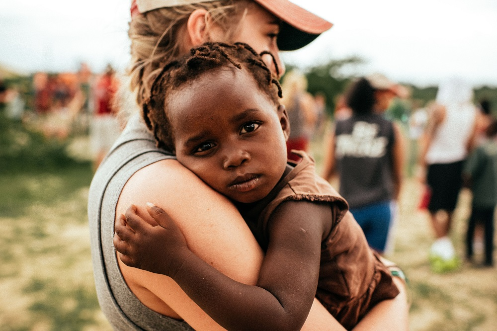 white woman holding a black child