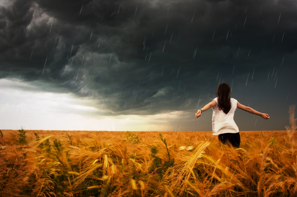 woman in a field in the rain